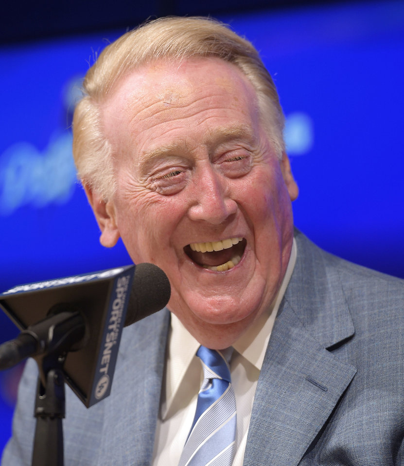 Photo - Los Angeles Dodgers announcer Vin Scully laughs as he speaks to the media prior to a baseball game against the Atlanta Braves, Wednesday, July 30, 2014, in Los Angeles. The 86-year-old Hall of Fame announcer said Tuesday that he will return for his record 66th season with the team in 2015. (AP Photo/Mark J. Terrill)