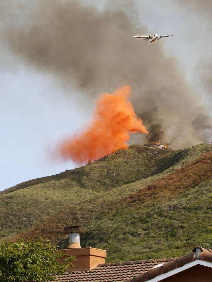 Photo - A plane drops fire retardant over the hills just south of Lompoc, Calif., Tuesday May13, 2014 to help control the fast moving Miguelito Fire. Wildfires pushed by gusty winds chewed through canyons parched by California's drought, prompting evacuation orders for 1,200 homes and businesses in Santa Barbara County. (AP Photo/The Santa Maria Times, Daniel Dreifuss)
