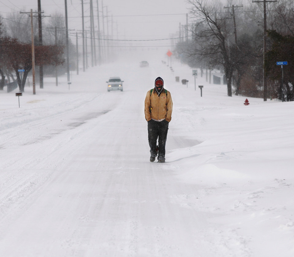 Photo - Troy Broyles walks along SE 15th Street in Midwest City as he returns home after taking a walk to a nearby grocery store. A  severe winter storm created whiteout conditions and caused snow drifts that made problems for the few motorists who ventured out Tuesday afternoon, Feb. 1, 2011.   Photo by Jim Beckel, The Oklahoman