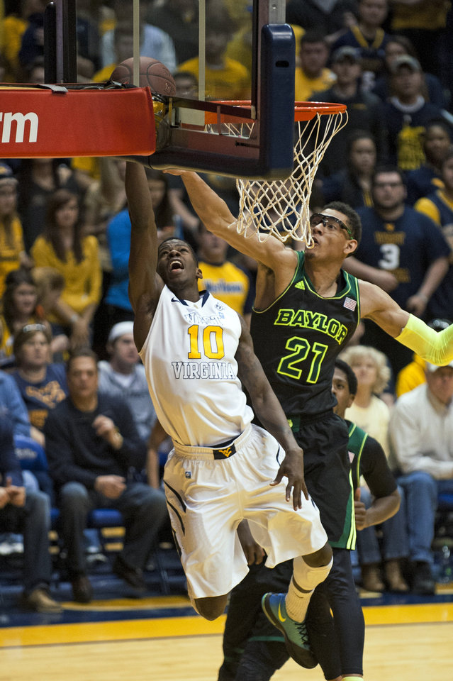 Photo - West Virginia's Eron Harris, left, lays in a basket as Baylor's Isaiah Austin defends during the first half of an NCAA college basketball game Saturday, Feb. 22, 2014, in Morgantown, W.Va. (AP Photo/Andrew Ferguson)
