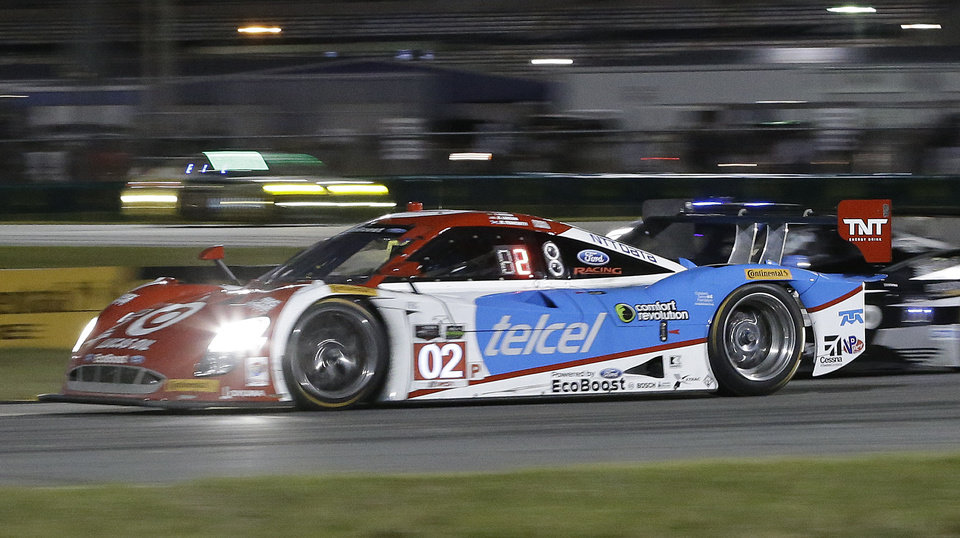 Photo - Tony Kanaan drives the Ganassi Riley DP through a turn during the IMSA Series Rolex 24 hour auto race at Daytona International Speedway in Daytona Beach, Fla., Saturday, Jan. 25, 2014.(AP Photo/John Raoux)