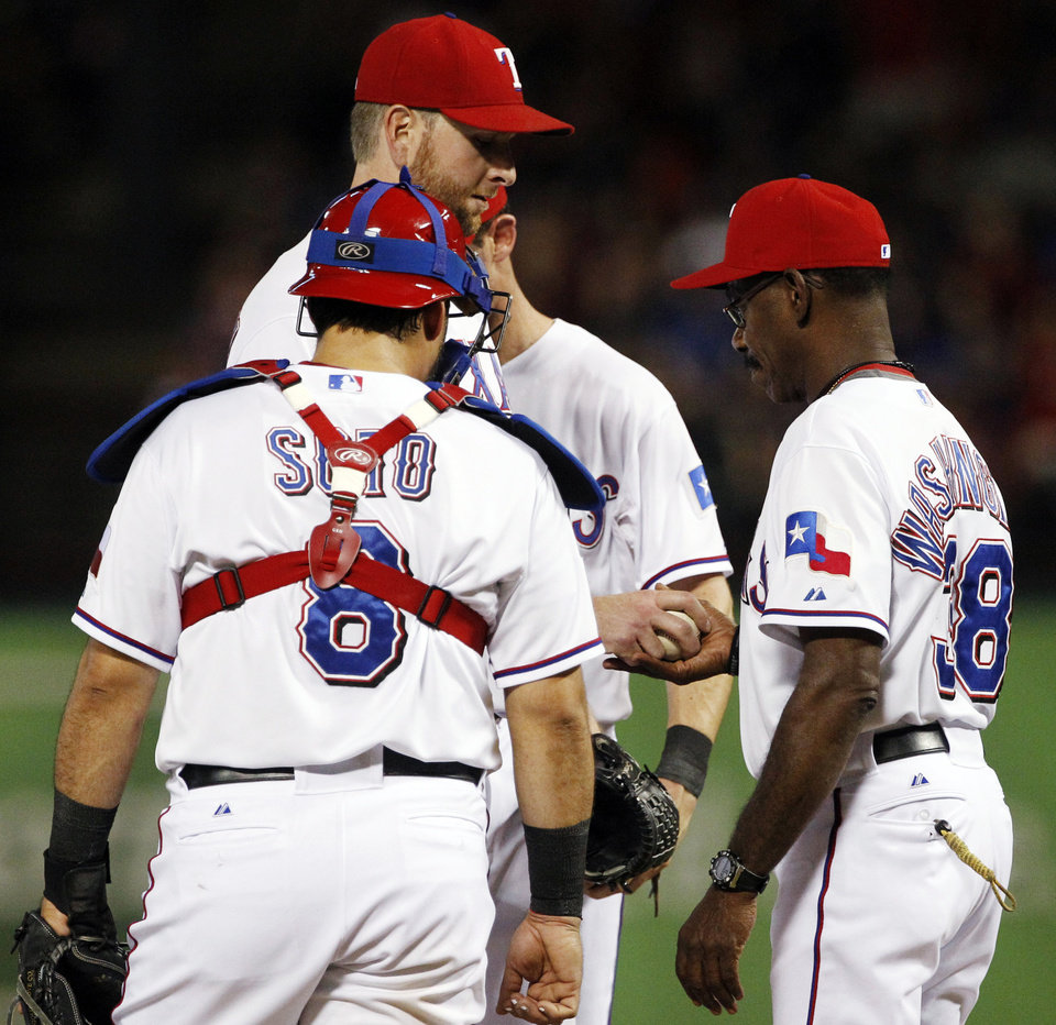 Photo -   Texas Rangers catcher Geovany Soto (8) watches as manager Ron Washington, right, takes the ball from starter Scott Feldman in the fourth inning of a baseball game against the Oakland Athletics, Tuesday, Sept. 25, 2012, in Arlington, Texas. (AP Photo/Tony Gutierrez)