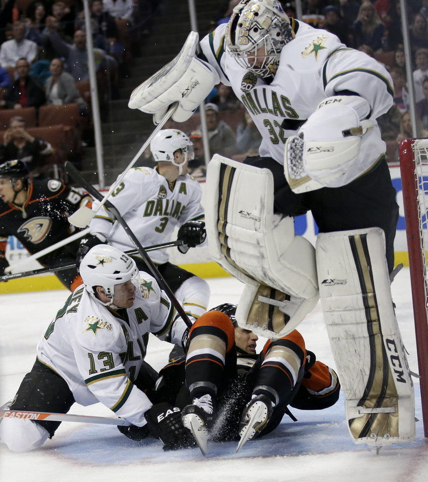 Dallas Stars goalie Kari Lehtonen, top, of Finland, jumps to avoid Dallas Stars' Ray Whitney, bottom left, and Anaheim Ducks' Andrew Cogliano during the second period of an NHL hockey game in Anaheim, Calif., Friday, April 5, 2013. (AP Photo/Jae C. Hong)