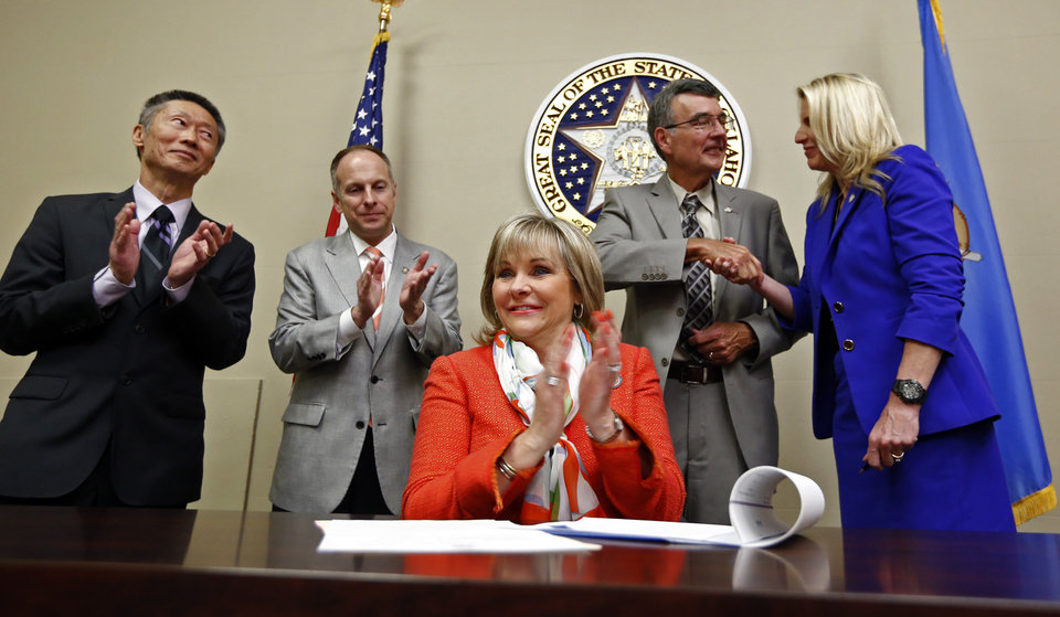 Photo -  Sen. Ervin Yen, Speaker of the House Jeff Hickman, Rep. Doug Cox and Sen. A.J. Griffin stand behind Gov. Mary Fallin on Tuesday, March 31, 2015, as she signs a prescription drug bill into law at the state Capitol in Oklahoma City. Photo by Steve Sisney, The Oklahoman   STEVE SISNEY -  THE OKLAHOMAN