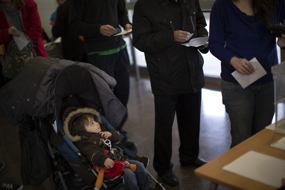A boy watches as voters holding ballot papers queue to cast their votes at a polling station in Barcelona, Spain, on Sunday, Nov. 25, 2012. Voters in Catalonia begin casting their ballots in regional elections that could determine the future shape of Spain. If voters give the regional government strong support, its leader pledged to hold a referendum asking Catalans if they'd prefer to split from Spain and go it alone in the 27-member EU. (AP Photo/Emilio Morenatti)