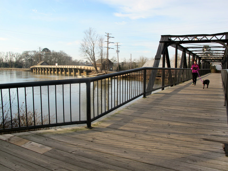 Photo - A jogger and her dog run across a bridge at the Columbia Riverfront Park in Columbia, S.C., on Jan. 25, 2014. For years, South Carolina's capital was known mainly to visitors as the seat of state government and the home of the University of South Carolina. But in recent years the area's varied attractions have been marketed as part of  tourism campaign that the area is