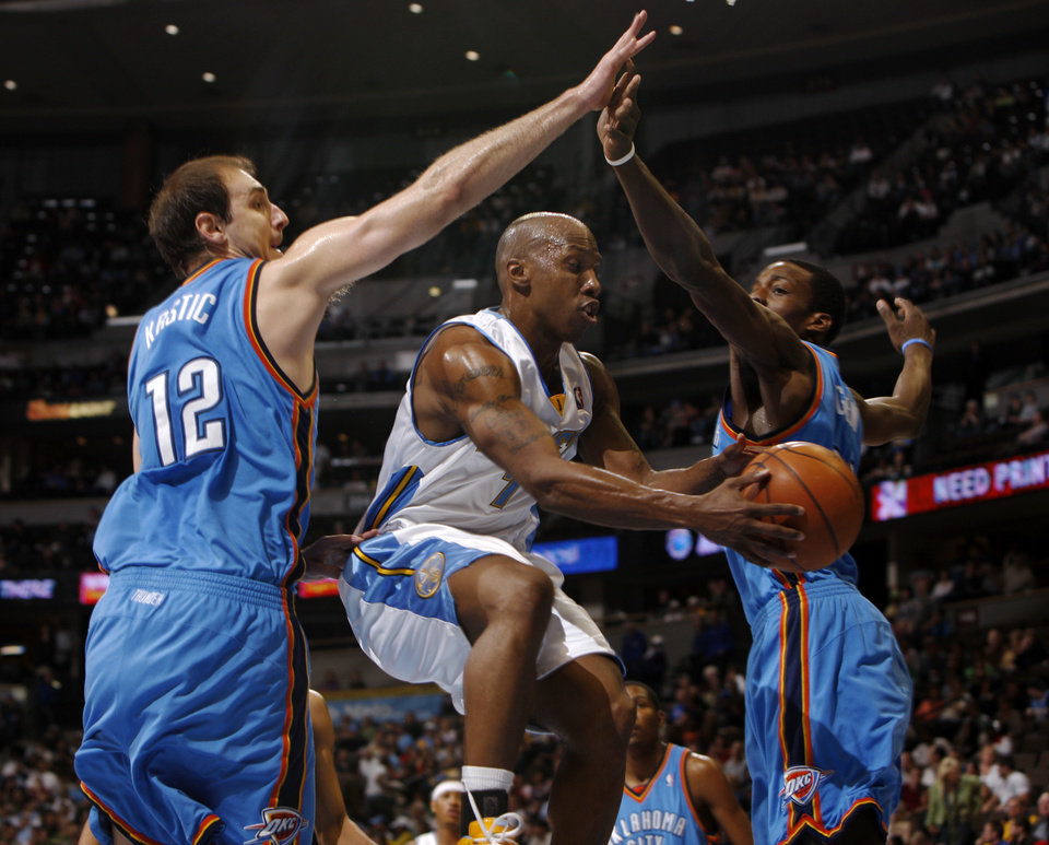 Photo - Denver Nuggets guard Chauncey Billups, center, slips between Oklahoma City Thunder center Nenad Krstic, left, of Serbia, and forward Jeff Green for a shot in the fourth quarter of the Nuggets' 122-112 victory in an NBA basketball game in Denver on Wednesday, April 8, 2009. (AP Photo/David Zalubowski) ORG XMIT: CODZ108