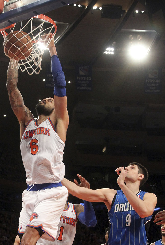 New York Knicks\' Tyson Chandler, left, dunks the ball as Orlando Magic\'s Nikola Vucevic watches during the first half of an NBA basketball game Wednesday, Jan. 30, 2013, at Madison Square Garden in New York. (AP Photo/Mary Altaffer)
