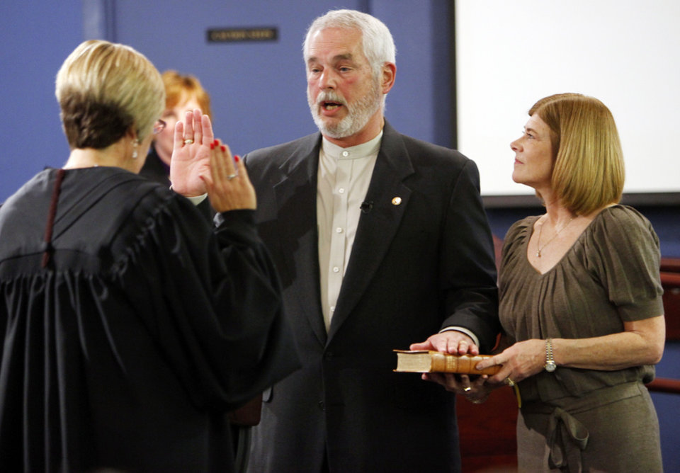 Charles Lamb, middle, next to his wife, Cheri Lamb, is sworn in as the mayor of Edmond by Diane Slayton, associate municipal judge, left, before an Edmond city council meeting at the city council chambers in Edmond, Okla., Monday, Nov. 14, 2011. Photo by Nate Billings, The Oklahoman