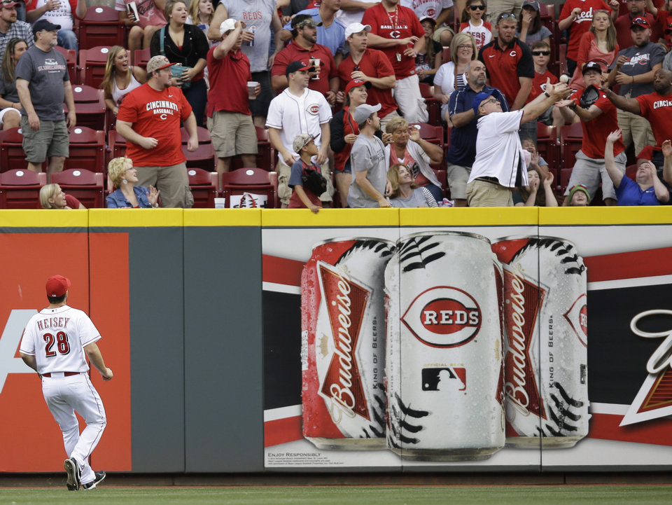 Photo - Cincinnati Reds center fielder Chris Heisey watches as a fan catches a home run hit by St. Louis Cardinals' Yadier Molina in the fourth inning of a baseball game, Saturday, May 24, 2014, in Cincinnati. (AP Photo/Al Behrman)