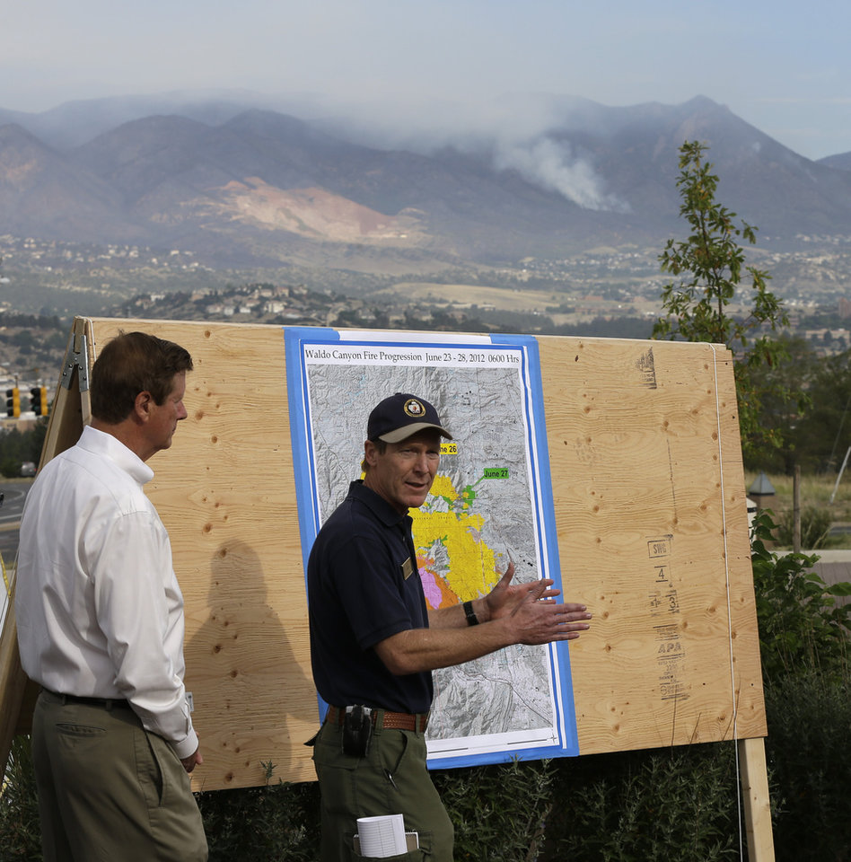 Photo -   Colorado Springs Mayor Steve Bach, left, looks on as Rich Harvey, incident commander, talks to the media during a news conference about the Waldo Canyon wildfire in Colorado Springs, Colo., Thursday, June 28, 2012. Colorado Springs officials said Thursday that hundreds of homes have been destroyed by the wildfire. (AP Photo/Chris Carlson)