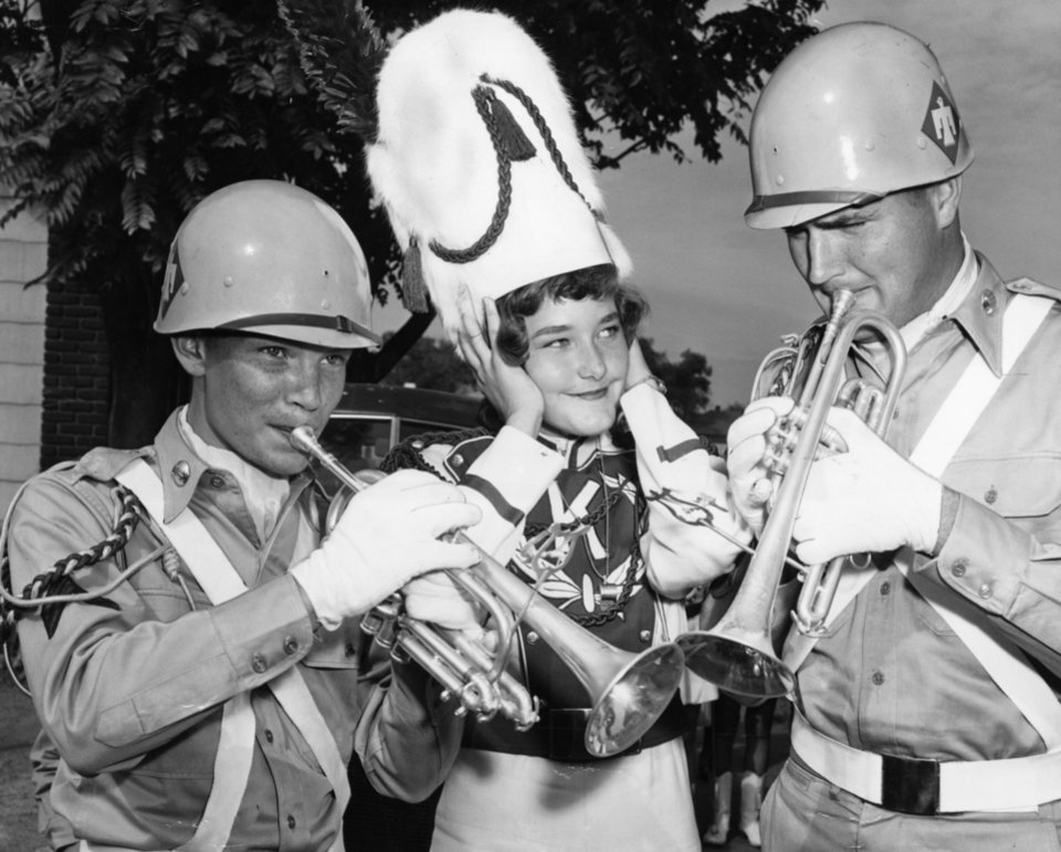 Photo - Thunderbird Music Not So Sweet to Visitor - Pretty Helen Easley, 15, of Kingston, member of the high school band there, wasn't too pleased with the taste of military music she heard here before Saturday's parade.  Cpl. Duane Cummings, left, Tecumseh, Neb., stationed with the 45th infantry division band at Enid, and S/Sgt. Roy McNaught, Kingfisher, also stationed at Enid, showed her how they could blow.  Staff photo by Jim Lucas.  Photo dated 09/25/1954 and published on 09/25/1954 in The Oklahoma City Times.
