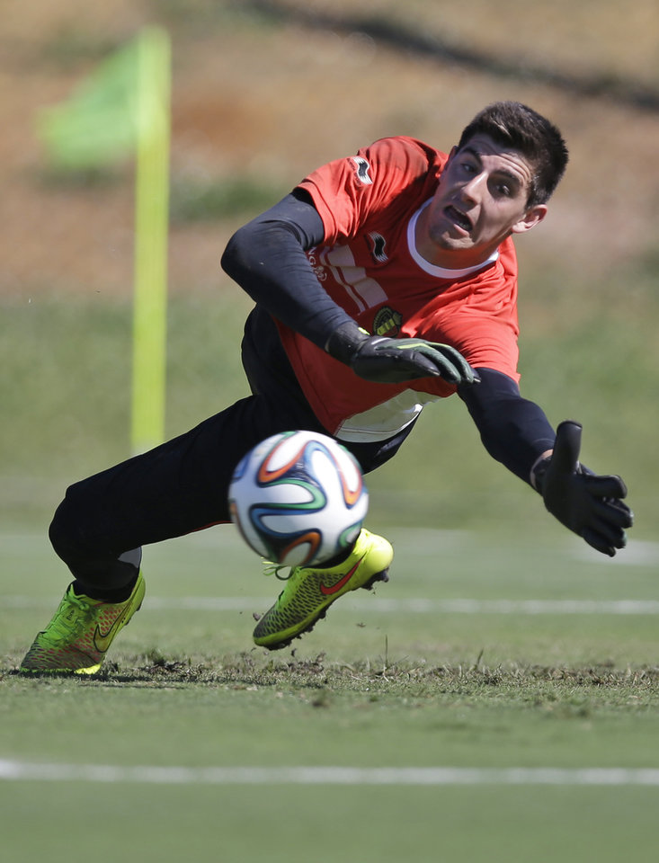 Photo - Belgium's goalkeeper Thibaut Courtois dives to catch the ball during a team training session in Mogi Das Cruzes, Brazil, Friday, June 13, 2014. Belgium play in group H of the 2014 soccer World Cup. (AP Photo/Andrew Medichini)