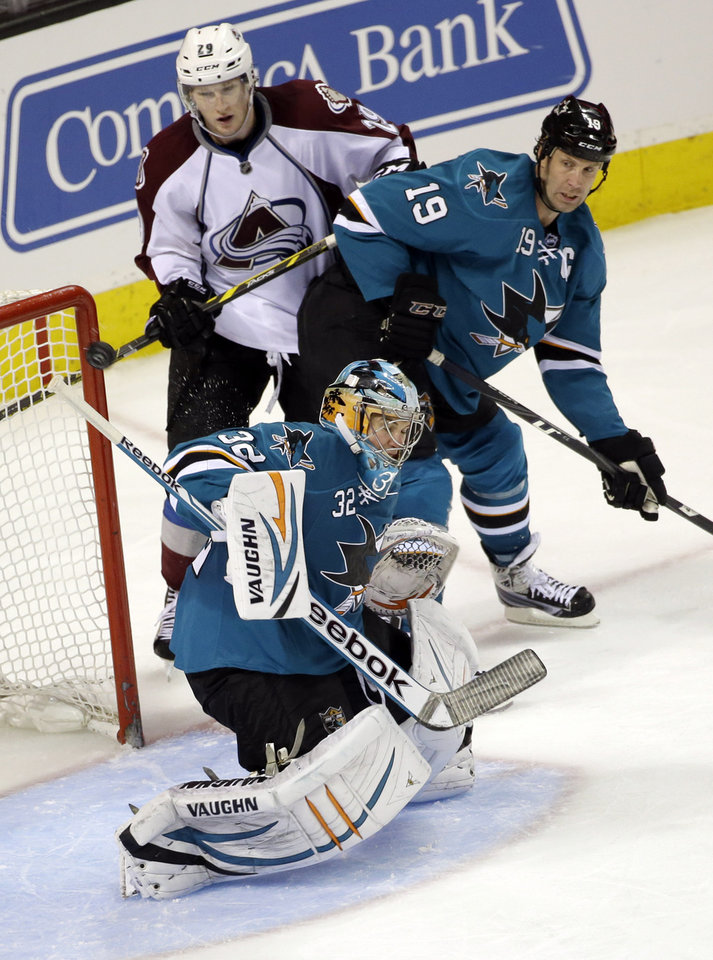 Photo - San Jose Sharks goalie Alex Stalock, bottom, deflects a shot on goal as Colorado Avalanche's Nathan MacKinnon, top left, and the Sharks' Joe Thornton (19) watch during the third period of an NHL hockey game Friday, April 11, 2014, in San Jose, Calif. San Jose won 5-1. (AP Photo/Marcio Jose Sanchez)