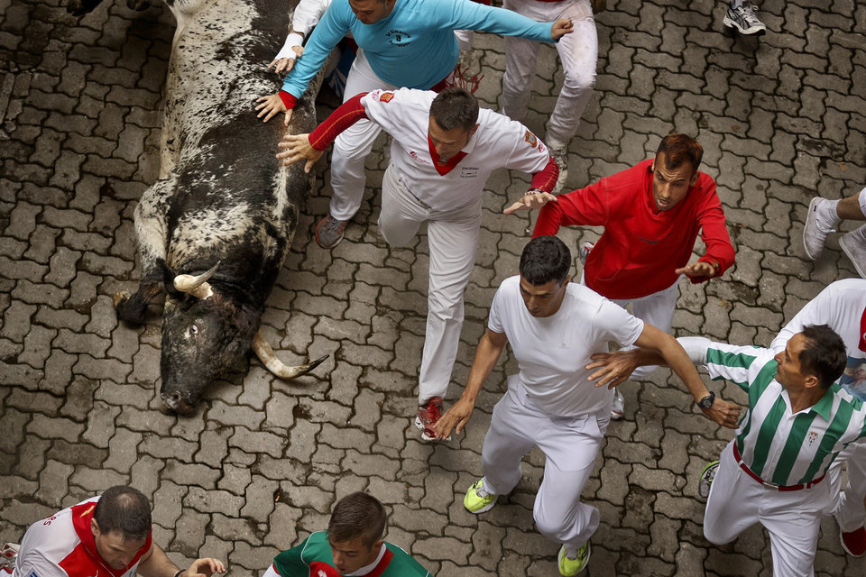 Photo - Revelers run while fighting bulls fall during the running of the bulls of the San Fermin festival, in Pamplona, Spain, Monday, July 7, 2014. Revelers from around the world arrive in Pamplona every year to take part on some of the eight days of the running of the bulls glorified by Ernest Hemingway's 1926 novel