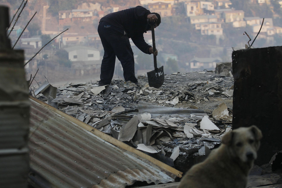 Photo - A man clears debris from his destroyed home after a large forest fire reached urban areas in Valparaiso, Chile, Sunday April 13, 2014. Authorities say the fires have destroyed hundreds of homes, forced the evacuation of thousands and claimed the lives of at least seven people.  ( AP Photo/ Luis Hidalgo)