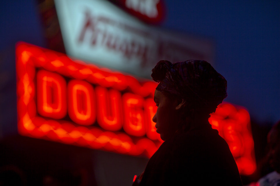 Photo - Burger King employee Keisha King, 23, stands during a protest outside a Krispy Kreme store, Thursday, May 15, 2014, in Atlanta. Calling for higher pay and the right to form a union without retaliation, fast-food chain workers in Atlanta protested Thursday as part of a wave of strikes and protests in 150 cities across the U.S. and 33 additional countries on six continents. (AP Photo/David Goldman)
