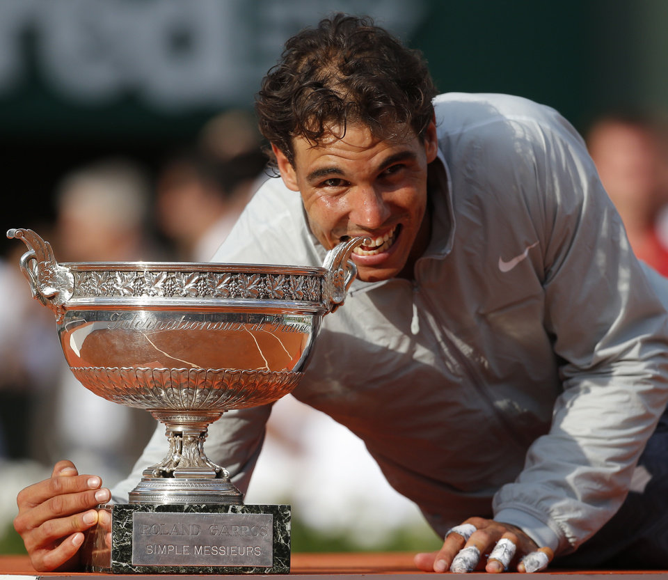 Photo - Spain's Rafael Nadal bites the trophy after winning the final of the French Open tennis tournament against Serbia's Novak Djokovic at the Roland Garros stadium, in Paris, France, Sunday, June 8, 2014. Nadal won in four sets 3-6, 7-5, 6-2, 6-4. (AP Photo/Michel Euler)