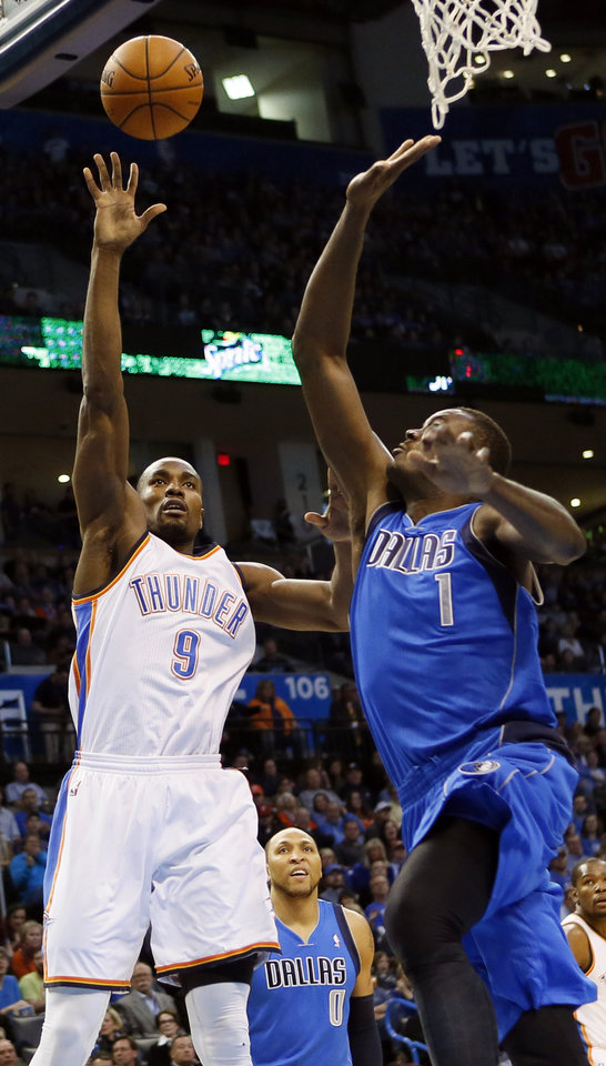 Photo - Oklahoma City's Serge Ibaka (9) shoots against Dallas' Samuel Dalembert (1) during an NBA basketball game between the Oklahoma City Thunder and the Dallas Mavericks at Chesapeake Energy Arena in Oklahoma City, Sunday, March 16, 2014. Photo by Nate Billings, The Oklahoman