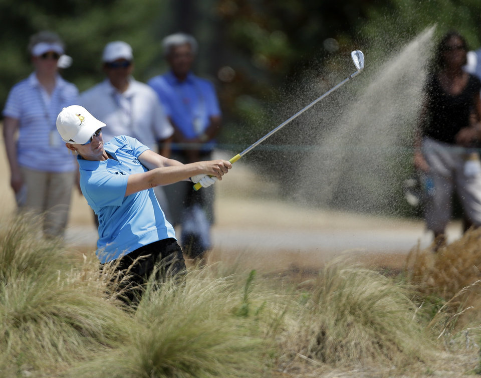 Photo - Karrie Webb, of Australia, hits from a waste area on the 13th hole during the first round of the U.S. Women's Open golf tournament in Pinehurst, N.C., Thursday, June 19, 2014. (AP Photo/Bob Leverone)