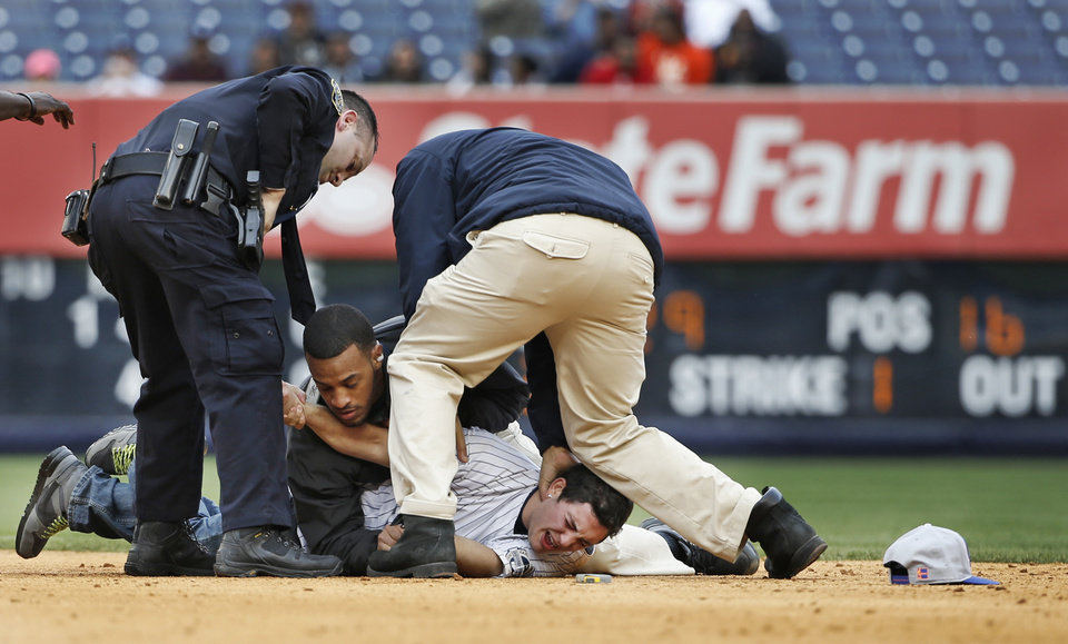 Photo - A police officer and two stadium security officers tackle a fan who ran onto the field in the eighth inning of the Yankees 14-5 loss to the Baltimore Orioles in the MLB American League baseball game at Yankee Stadium in New York, Tuesday, April 8, 2014. Two fans made it onto the field behind second base in the incident, which interrupted play. Both fans were tackled and escorted off the field as players watched. (AP Photo/Kathy Willens)