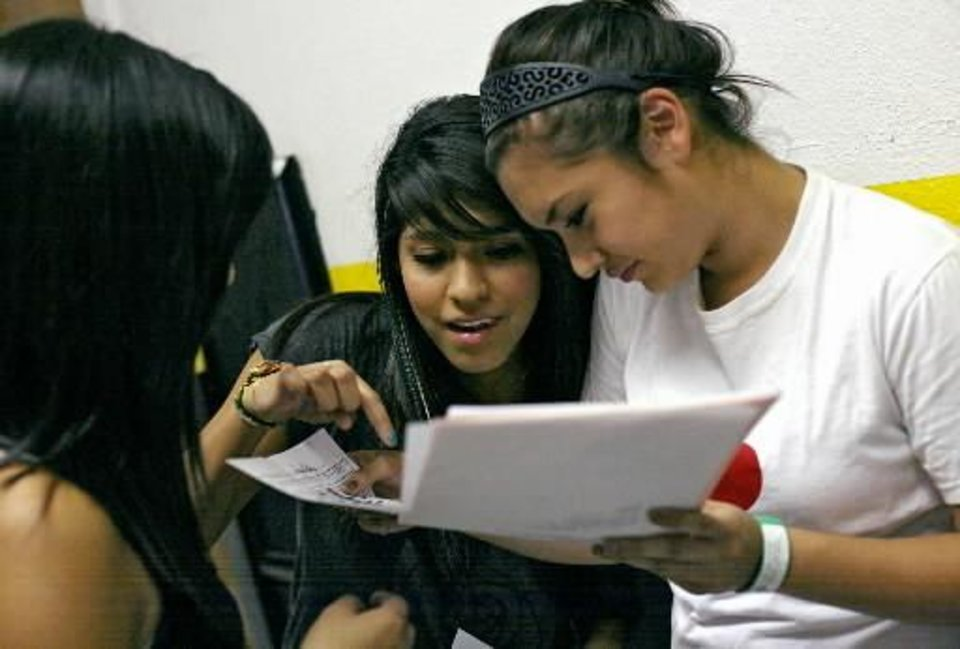 Sophomores Laura Ortiz (center) and Monica Serna (right) compare their schedules as they talk in the hallway during the Back 2 School Bash at Santa Fe South Charter High School in Oklahoma City on Monday, Aug. 1, 2011. Photo by John Clanton