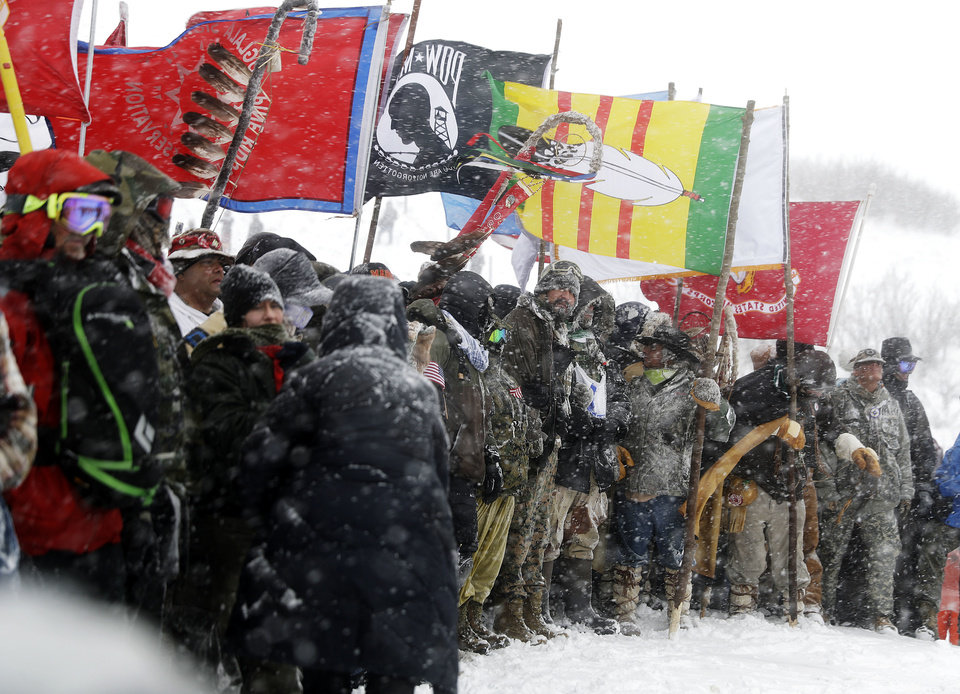 Photo - Military veterans and Native American tribal elders come to a stop for a ceremonial prayer during a march to a closed bridge across from the Dakota Access oil pipeline site in Cannon Ball, N.D., Monday, Dec. 5, 2016. (AP Photo/David Goldman)