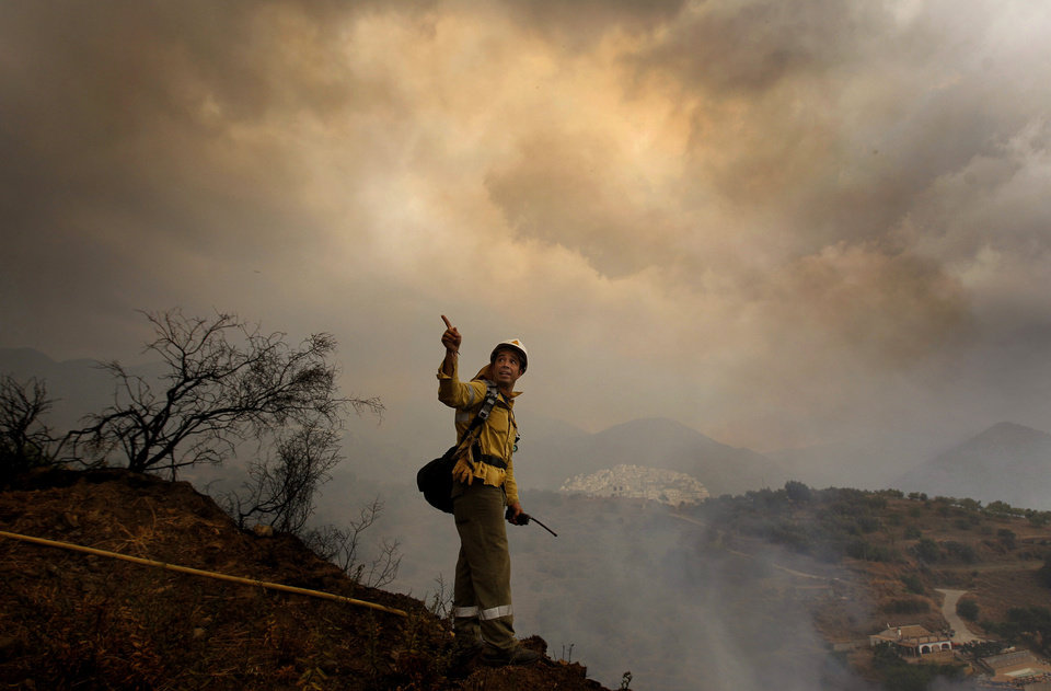 Photo -   A firefighter works amid smoke from a raging forest fire in Ojen, southern Spain, Friday, Aug. 31, 2012. Spanish officials say some 4,000 people have been evacuated from their houses as a wildfire abetted by strong winds spread rapidly through hills around the popular southern tourist city of Marbella. (AP Photo/Sergio Torres)