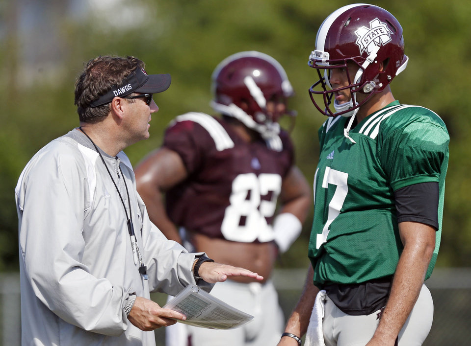 Photo - Mississippi State quarterback Tyler Russell, right, confers with football coach Dan Mullen during an NCAA college football practice in Starkville, Miss., Saturday, Aug. 10, 2013. High humidity mixed with high temperatures have marked most of the football training camps this summer. (AP Photo/Rogelio V. Solis)  ORG XMIT: MSRS102
