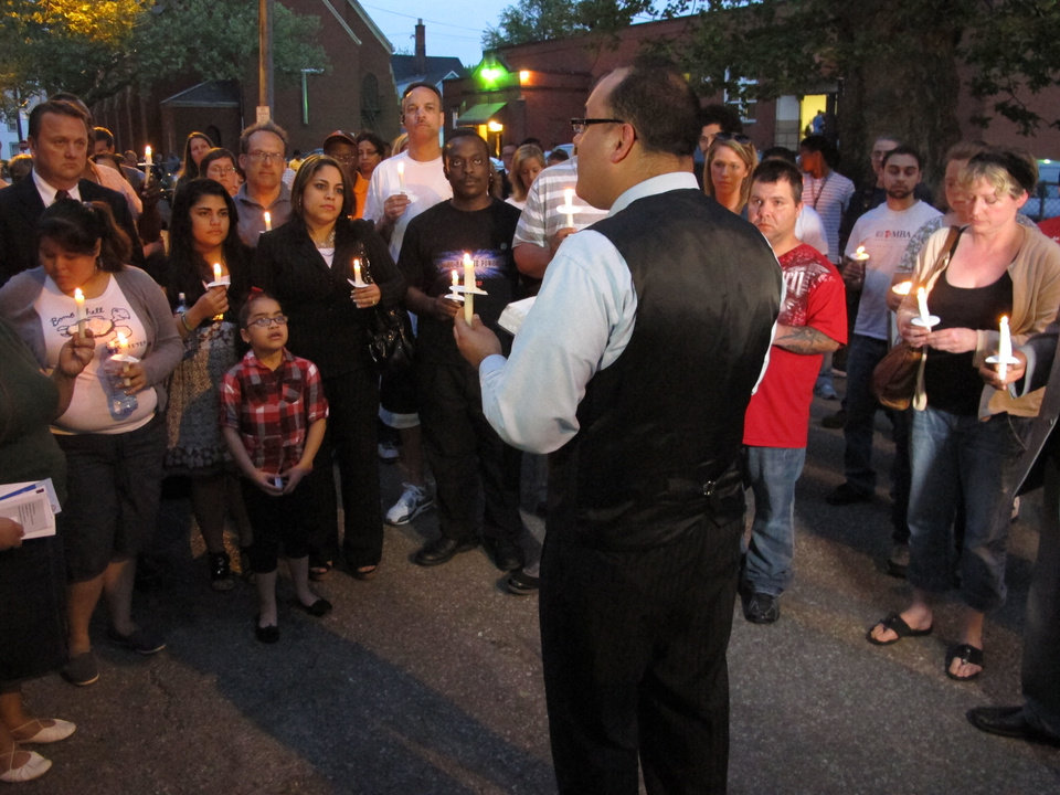 Photo - Pastor Omar Medina leads a candlelight prayer vigil on Thursday, May 9, 2013, in Cleveland, half a block from the house where investigators say three women were imprisoned by a man for nearly a decade. Medina told participants in the vigil that the message of the women's escape was never to lose hope. (AP Photo/Andrew Welsh-Huggins)