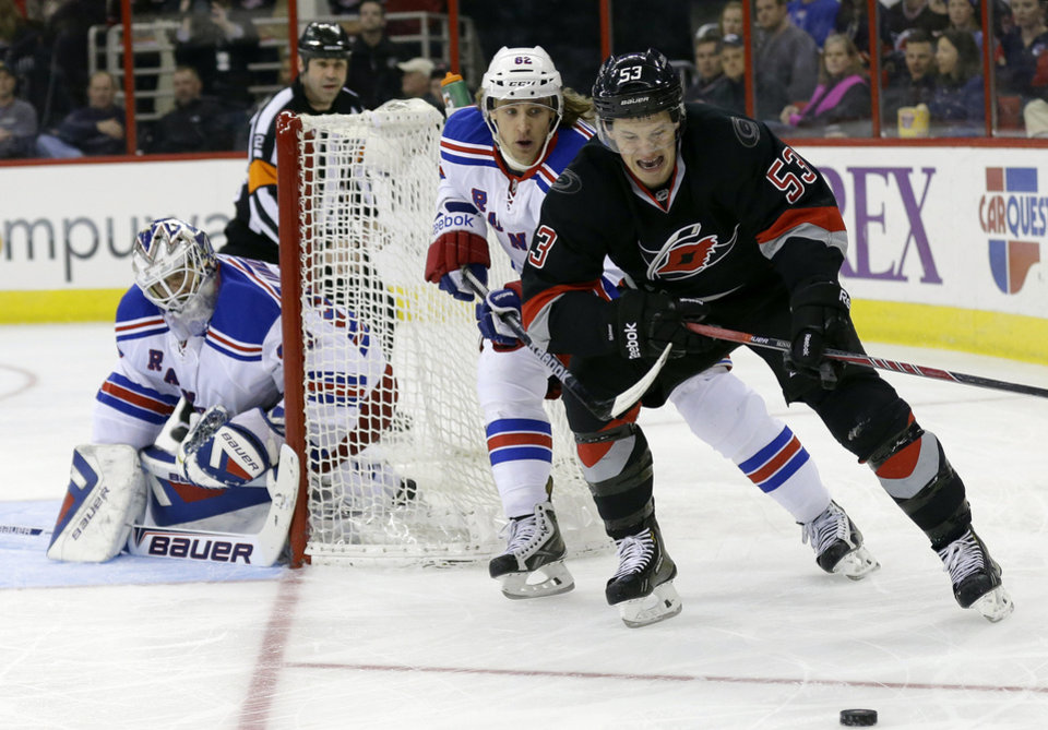 Photo - Carolina Hurricanes' Jeff Skinner (53) chases the puck as New York Rangers' Carl Hagelin (62) and goalie Henrik Lundqvist, of Sweden, defend the goal during the second period of an NHL hockey game in Raleigh, N.C., Friday, March 7, 2014. (AP Photo/Gerry Broome)