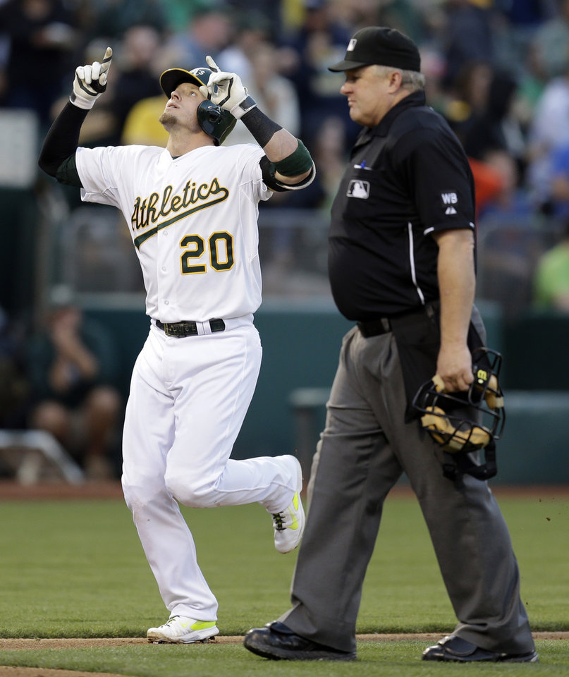 Photo - Oakland Athletics' Josh Donaldson (20) celebrates as he runs past home plate umpire Bill Miller after hitting a home run against the Toronto Blue Jays in the third inning of a baseball game on Saturday, July 5, 2014, in Oakland, Calif. (AP Photo/Ben Margot)