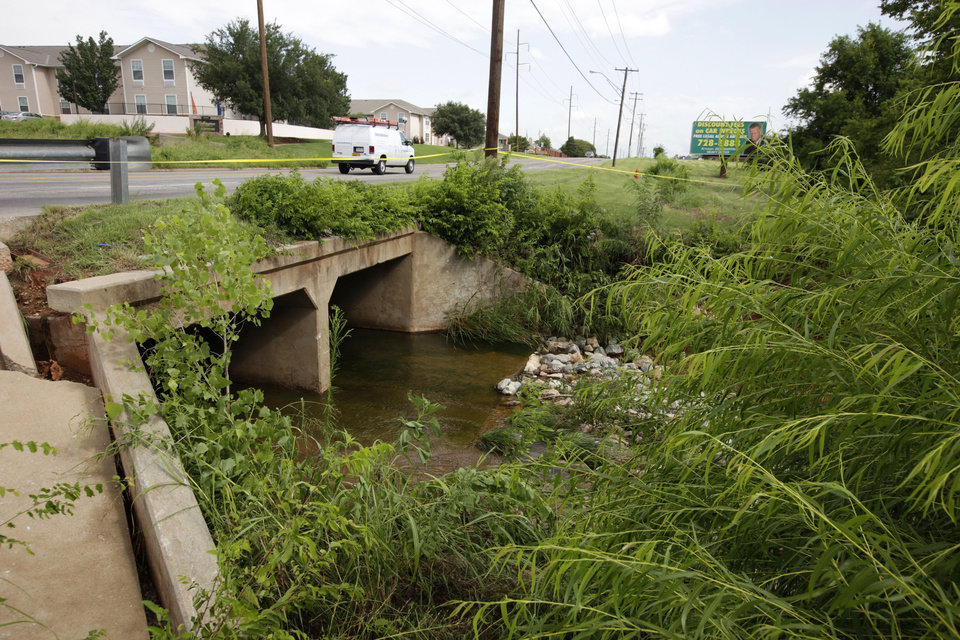Photo - A drainage ditch runs under Pennsylvania Ave., looking north. Caution tape runs along the road  Friday where a man was swept into floodwaters near NW 118 and Barnes Avenue. His body was found near NW 125 and Penn. Photo by David McDaniel, The Oklahoman  David McDaniel
