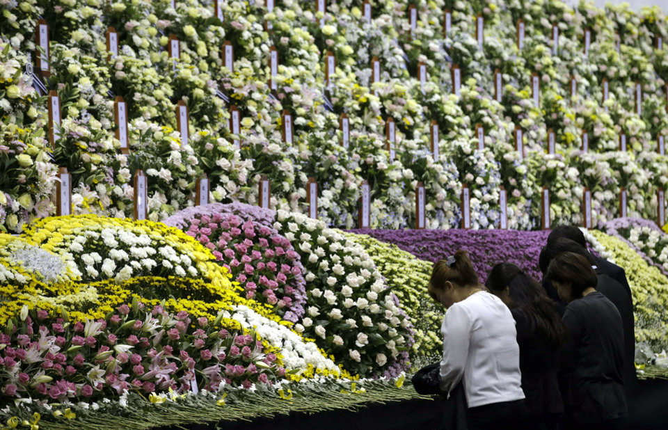 Photo - Relatives pay tribute to the victims of the sunken ferry Sewol at a group memorial altar in Ansan, south of Seoul, South Korea, Wednesday, April 30, 2014. Two weeks after the ferry sank off South Korea's southern cost, divers have recovered over 200 bodies from the wreckage, but they fought strong currents and floating debris inside the ship Wednesday as they searched for 90 passengers still missing.(AP Photo/Lee Jin-man)