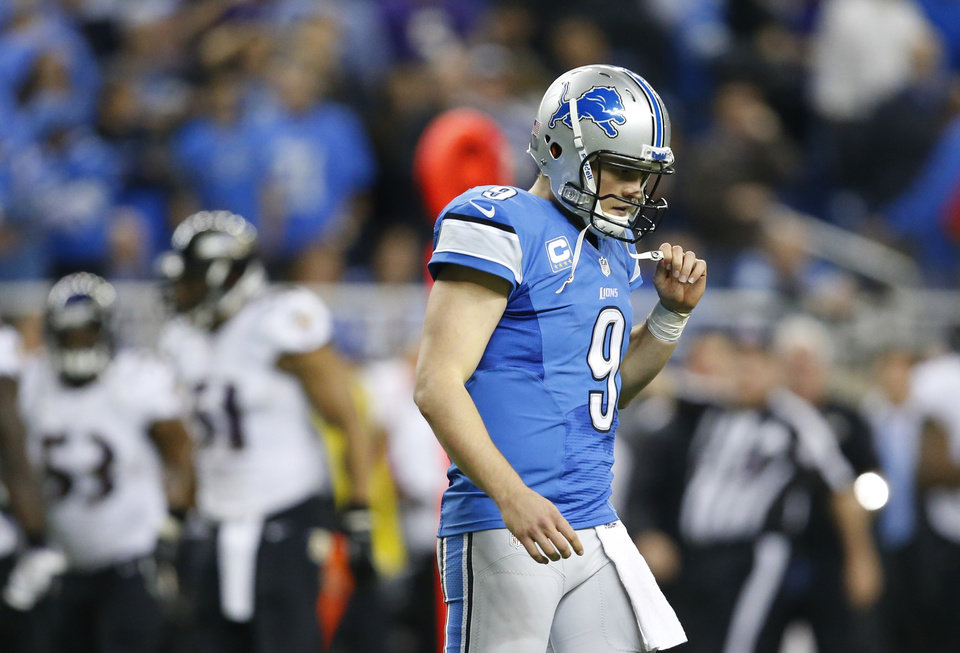 Photo - Detroit Lions quarterback Matthew Stafford (9) walks off the field after Baltimore Ravens free safety Matt Elam (26) intercepted his pass during the fourth quarter of an NFL football game in Detroit, Monday, Dec. 16, 2013. (AP Photo/Rick Osentoski)