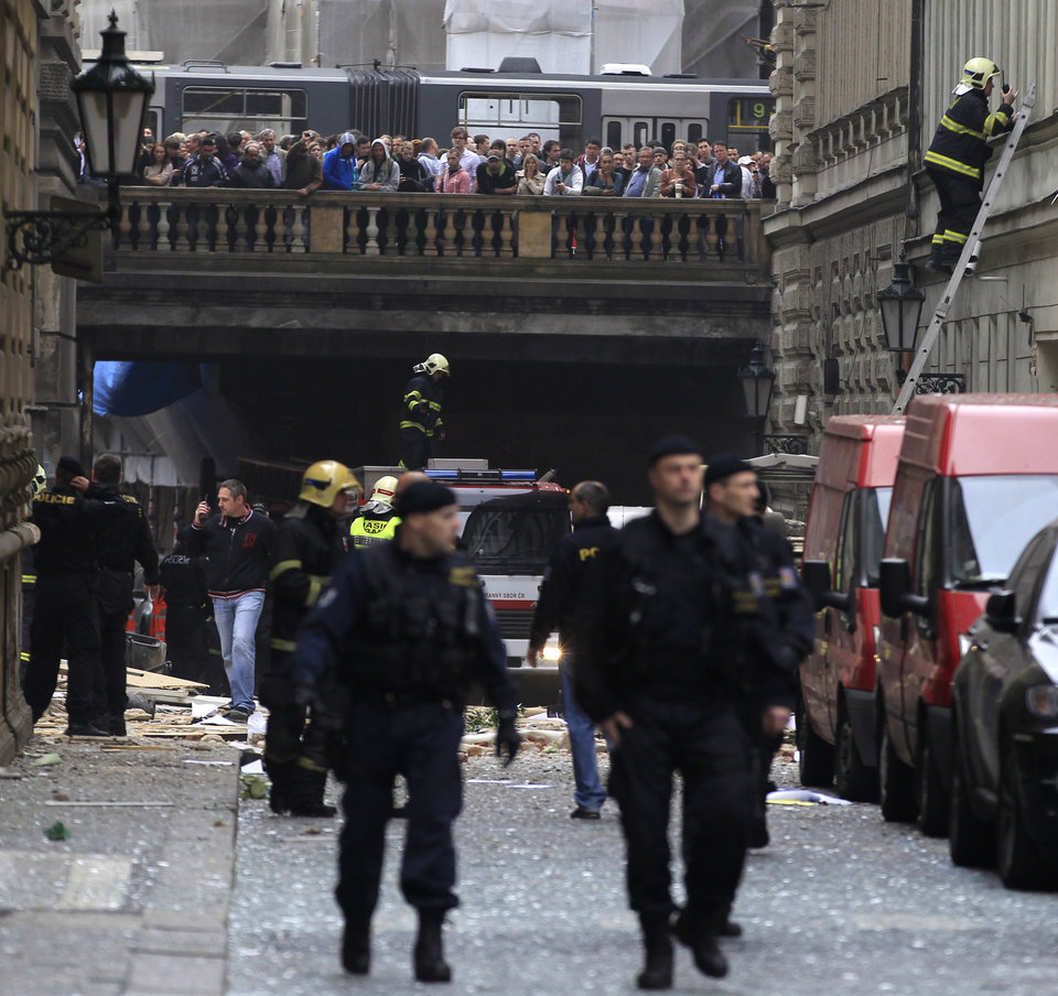 Photo - Policemen and firefighters inspect the scene of an explosion in downtown Prague, Czech Republic, Monday, April 29, 2013. Police said a powerful explosion has damaged a building in the center of the Czech capital and they believe some people are buried in the rubble. (AP Photo/Petr David Josek)