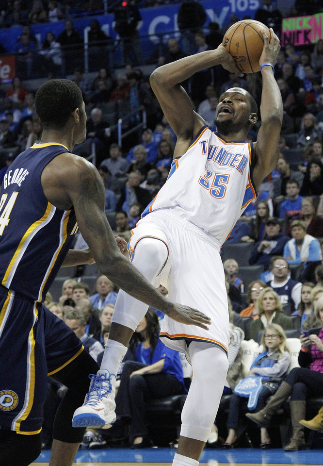 Photo - Oklahoma City Thunder forward Kevin Durant (35) shoots in front of Indiana Pacers forward Paul George (24) in the second quarter of an NBA basketball game in Oklahoma City, Sunday, Dec. 9, 2012. (AP Photo/Sue Ogrocki)