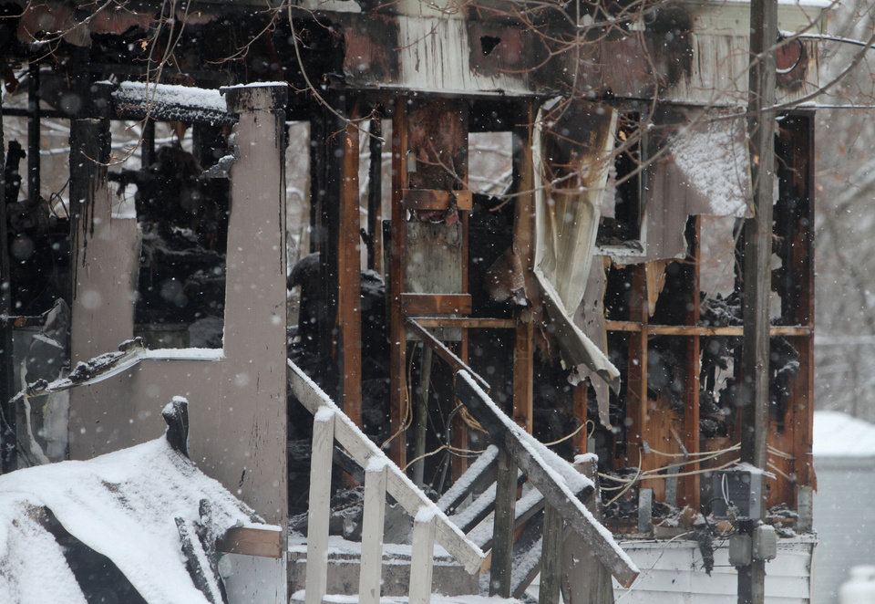 Photo - In this Jan. 20, 2014 photo, snow falls on the burned out shell of a mobile home in Penfield, N.Y. Firefighters are calling eight-year-old Tyler Doohan a hero after his actions alerted and saved six of the nine people living in the 14-foot-by-60-foot trailer after fire broke out in the early morning hours of Monday. Doohan died while trying to save his disabled grandfather from the flames. His grandfather and an uncle perished. (AP Photo/Rochester Democrat and Chronicle, Tina McIntyre-Yee)