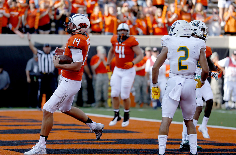 Photo - Oklahoma State's Taylor Cornelius (14) scores a touchdown in the fourth quarter during the college football game between the Oklahoma State Cowboys (OSU) and the Southeastern Louisiana Lions at Boone Pickens Stadium in Stillwater, Okla., Saturday, Sept. 12, 2015. Photo by Sarah Phipps, The Oklahoman