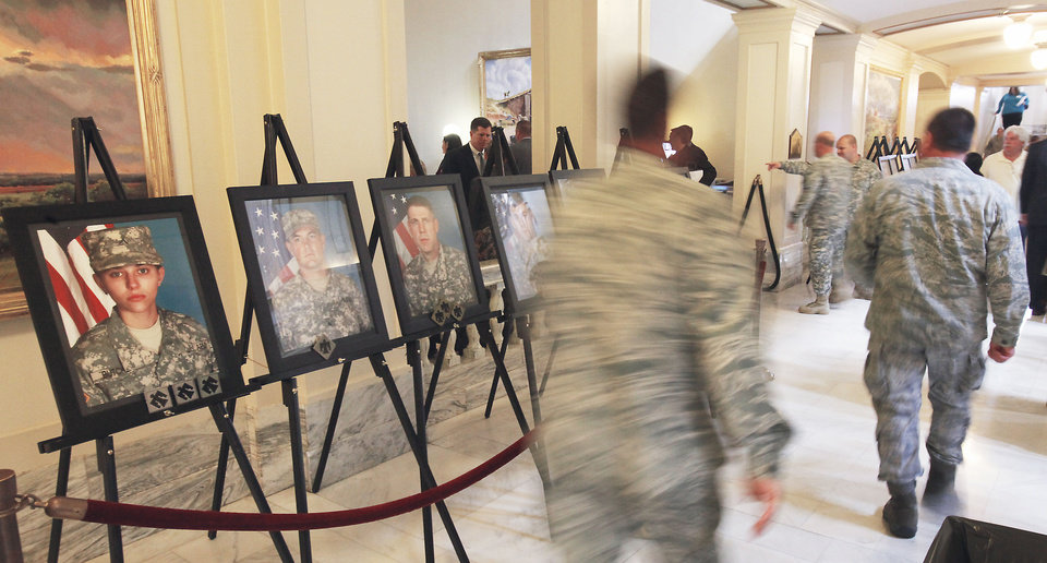 Soldiers walk past portraits of fallen guardsmen on Tuesday after the joint session of the Legislature to recognize the Oklahoma National Guard�s 45th Infantry Brigade at the state Capitol. Photo By David McDaniel, The Oklahoman