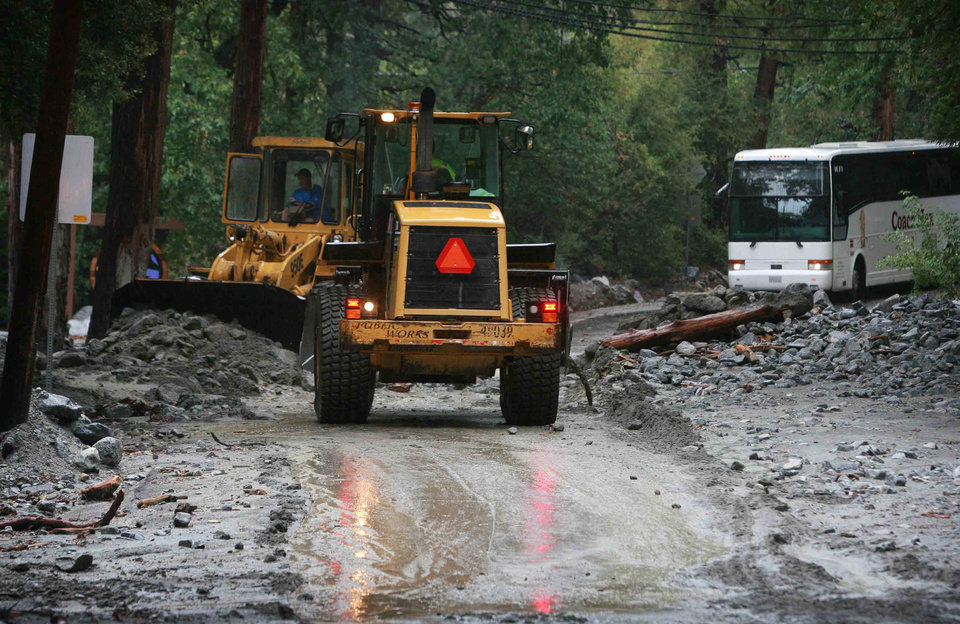 Photo - In this Sunday, Aug. 3, 2014 photo, emergency workers clear one of several rock and mudslides blocking Valley of the Falls Drive following a downpour in Forest Falls, Calif. Crews on Monday have cleared several feet of mud, rocks and debris that had blocked San Bernardino County roads, stranding some 2,500 people in the rural communities of Oak Glen and Forest Falls. (AP Photo/The Press-Enterprise, David Bauman)  MAGS OUT; MANDATORY CREDIT