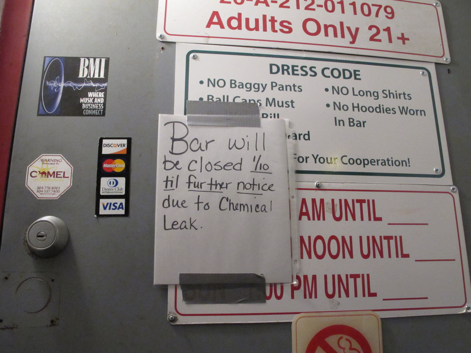 Photo - A sign outside the Red Carpet, a bar popular with Capitol employees, notifying customers it's closed because of a chemical spill that caused a do-not-use order for the water supply in the capital and surrounding areas on Thursday, Jan. 9, 2014 in Charleston, W.Va. (AP Photo/Brendan Farrington)