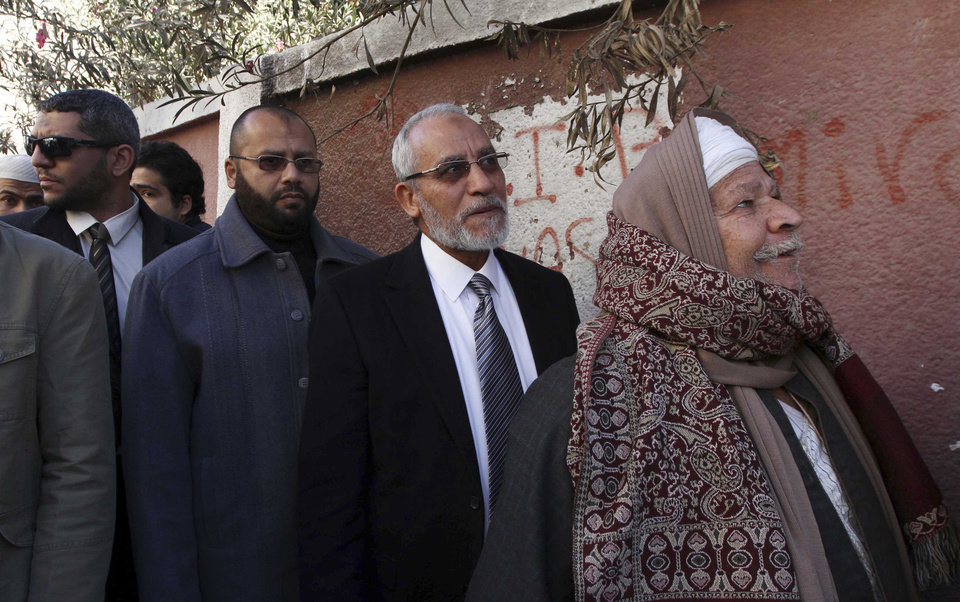 Photo - Muslim Brotherhood leader Mohammed Badie, second right, waits in line outside a polling place in Beni Suef, Egypt, to vote on a constitution drafted by Islamist supporters of Presudent Mohammed Morsi, Saturday, Dec. 22, 2012. (AP Photo/Ahmed Ramadan)
