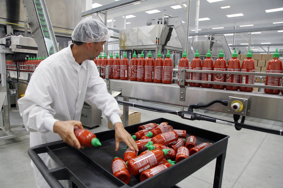 Photo - Sriracha chili sauce is produced at the Huy Fong Foods factory in Irwindale, Calif., on Tuesday, Oct 29, 2013. The maker of Sriracha hot sauce is under fire for allegedly fouling the air around its Southern California production site. The city of Irwindale filed a lawsuit in Los Angeles Superior Court Monday asking a judge to stop production at the Huy Fong Foods factory, claiming the chili odor emanating from the facility is a public nuisance. (AP Photo/Nick Ut)