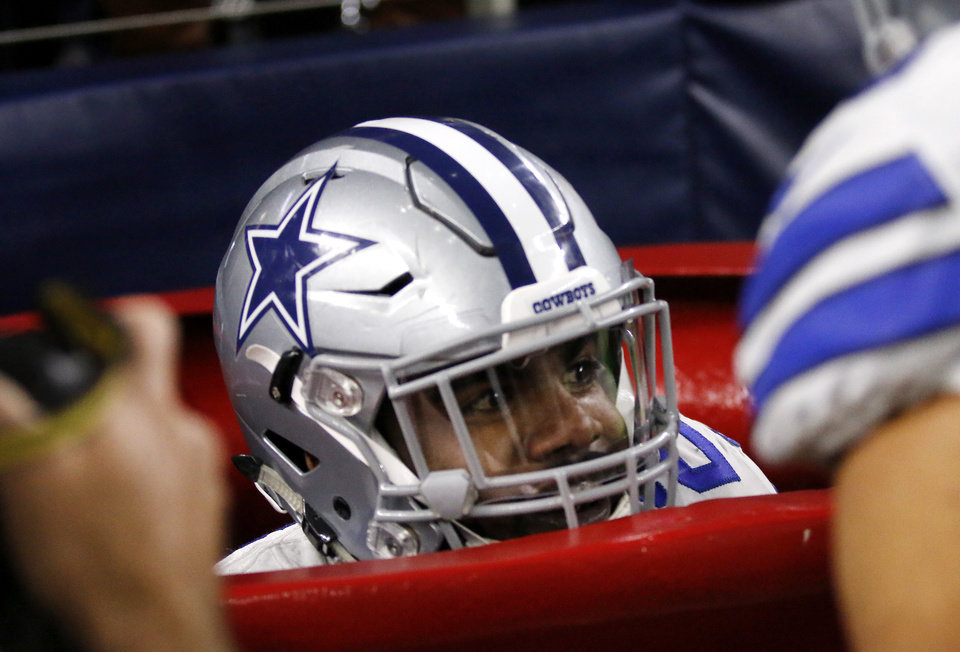 Photo -  Dallas Cowboys running back Ezekiel Elliott peeks out of a large Salvation Army kettle after scoring a touchdown in last week's game. [AP Photo]