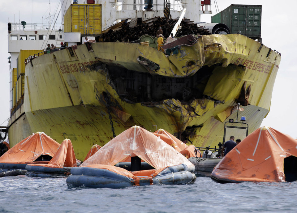 Photo - A cluster of life rafts floats near the cargo ship Sulpicio Express Siete Saturday Aug. 17, 2013, a day after it collided with a passenger ferry off the waters of Talisay city, Cebu province in central Philippines. Divers combed through a sunken ferry Saturday to retrieve the bodies of more than 200 people still missing from an overnight collision with a cargo vessel near the central Philippine port of Cebu that sent passengers jumping into the ocean and leaving many others trapped. At least 28 were confirmed dead and hundreds rescued. The captain of the ferry MV Thomas Aquinas, which was approaching the port late Friday, ordered the ship abandoned when it began listing and then sank just minutes after collision with the MV Sulpicio Express, coast guard deputy chief Rear Adm. Luis Tuason said. (AP Photo/Bullit Marquez)