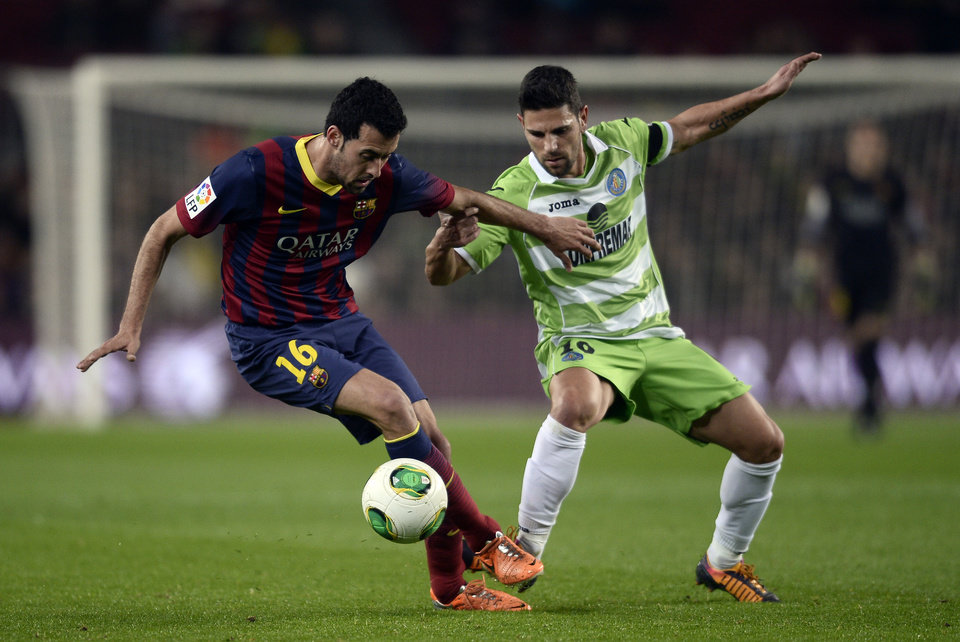 Photo - FC Barcelona's Sergio Busquets, left, duels for the ball against Getafe´s Jaime Gavilan during a Copa del Rey soccer match at the Camp Nou stadium in Barcelona, Spain, Wednesday, Jan. 8, 2014. (AP Photo/Manu Fernandez)
