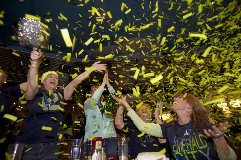 Photo - Seattle Seahawks fans celebrate while watching Super Bowl XLVIII at Big Al's in Vancouver, Wash., Sunday, Feb. 2, 2014. Seattle defeated the Denver Broncos 43-8. (AP Photo/The Columbian, Steven Lane)