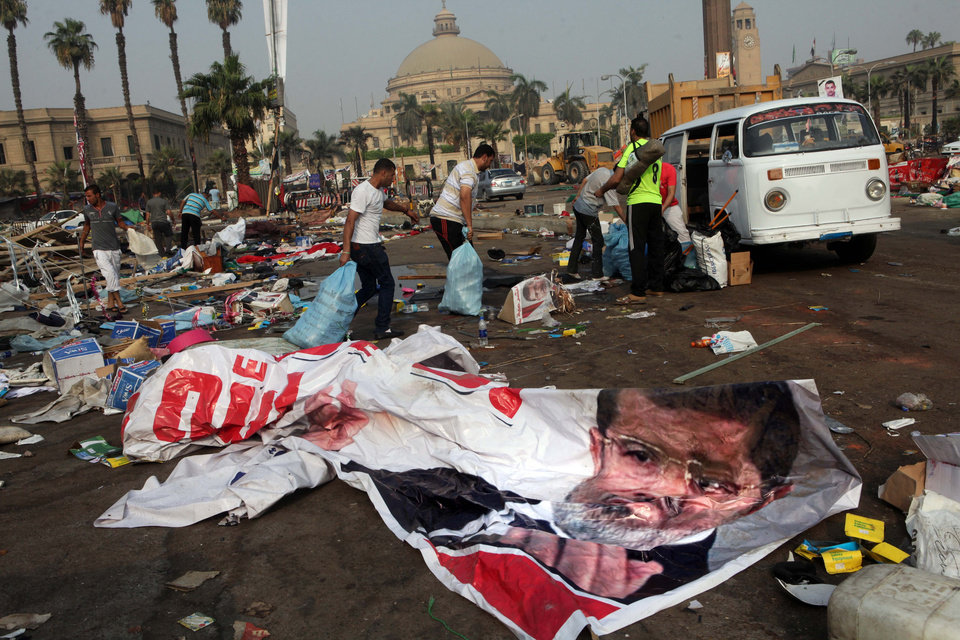 Photo - Egyptians remove valuables they collected from debris in a protest camp next to a banner depicting Egypt's ousted President Mohammed Morsi in Nahda Square, Giza, Cairo, Egypt, Thursday, Aug. 15, 2013. Egypt faced a new phase of uncertainty on Thursday after the bloodiest day since its Arab Spring began, with over 300 people reported killed and thousands injured as police smashed two protest camps of supporters of the deposed Islamist president. Wednesday's raids touched off day-long street violence that prompted the military-backed interim leaders to impose a state of emergency and curfew, and drew widespread condemnation from the Muslim world and the West, including the United States. (AP Photo/Amr Nabil)