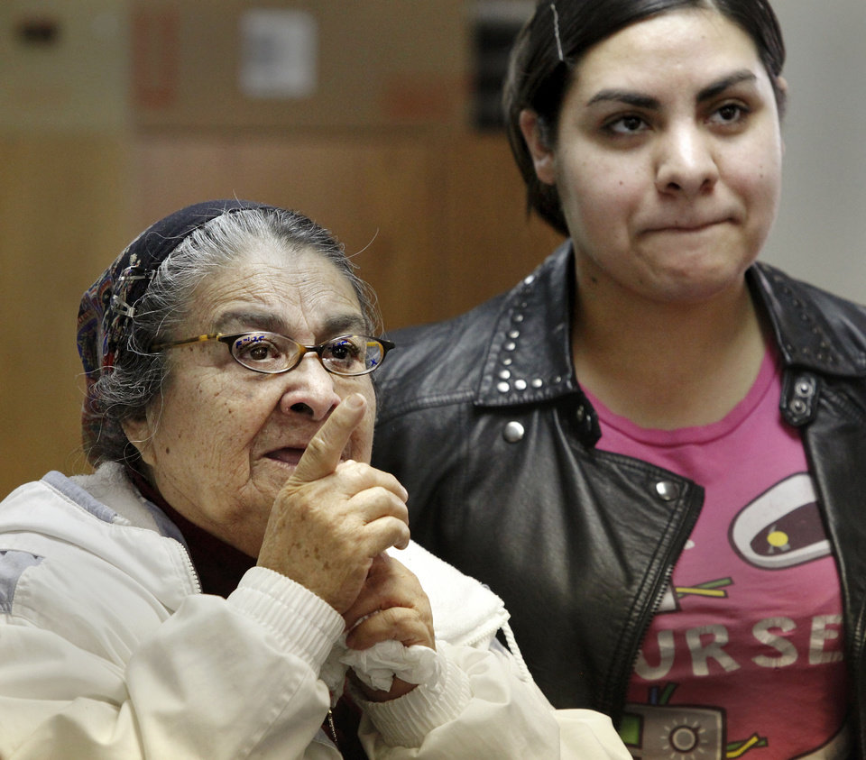 Guadalupe Fuentes, left, points to letters on the wall as she reads an eye chart to her daughter, Rosa Rodriguez, as Fuentes tries different pairs of glasses to improve her vision. Photo by Jim Beckel, The Oklahoman <strong>Jim Beckel - THE OKLAHOMAN</strong>